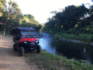 Black and red ATV by a river