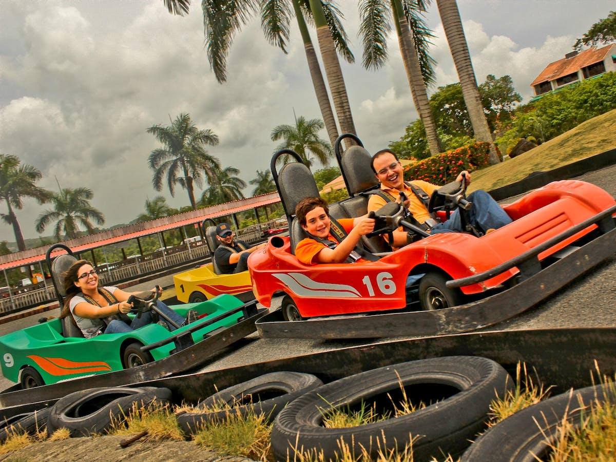 People driving orange and green go-karts