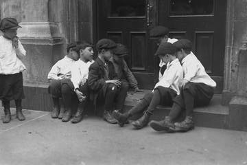 Black and white photo of young boys sitting on house steps in New York City