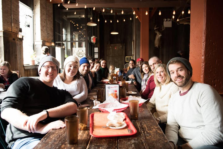 Group of tourists sitting at large table in Brooklyn restaurant