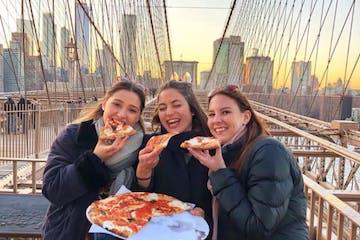 three women eating pizza