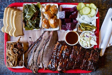 bbq brisket and sides on a large wooden platter