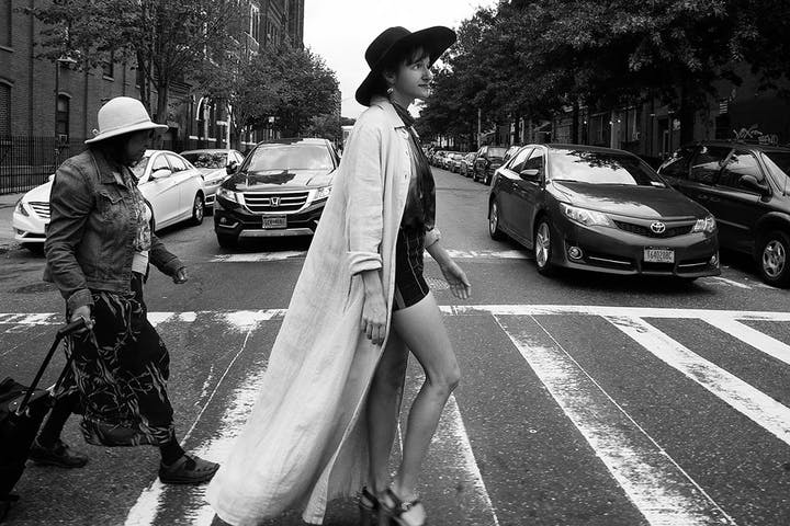 black and white photo of woman walking across a crosswalk wearing trendy clothing