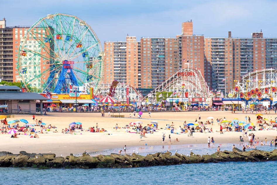 people on the beach at coney island with buildings and luna park in the background