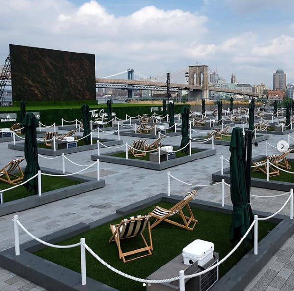 outdoor picnic area on a roof with NYC buildings in the background