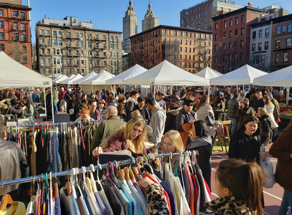 a group of people shopping at an outdoor flea marke