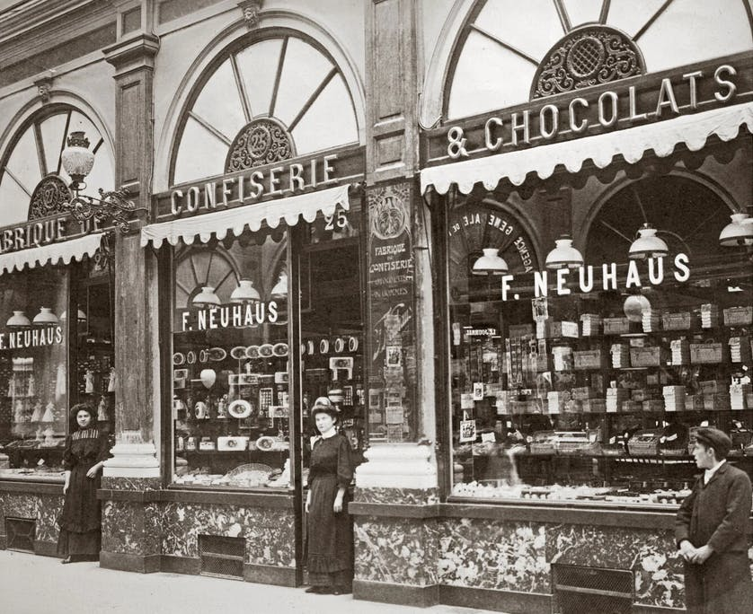 an old photo of a woman standing in front of a store