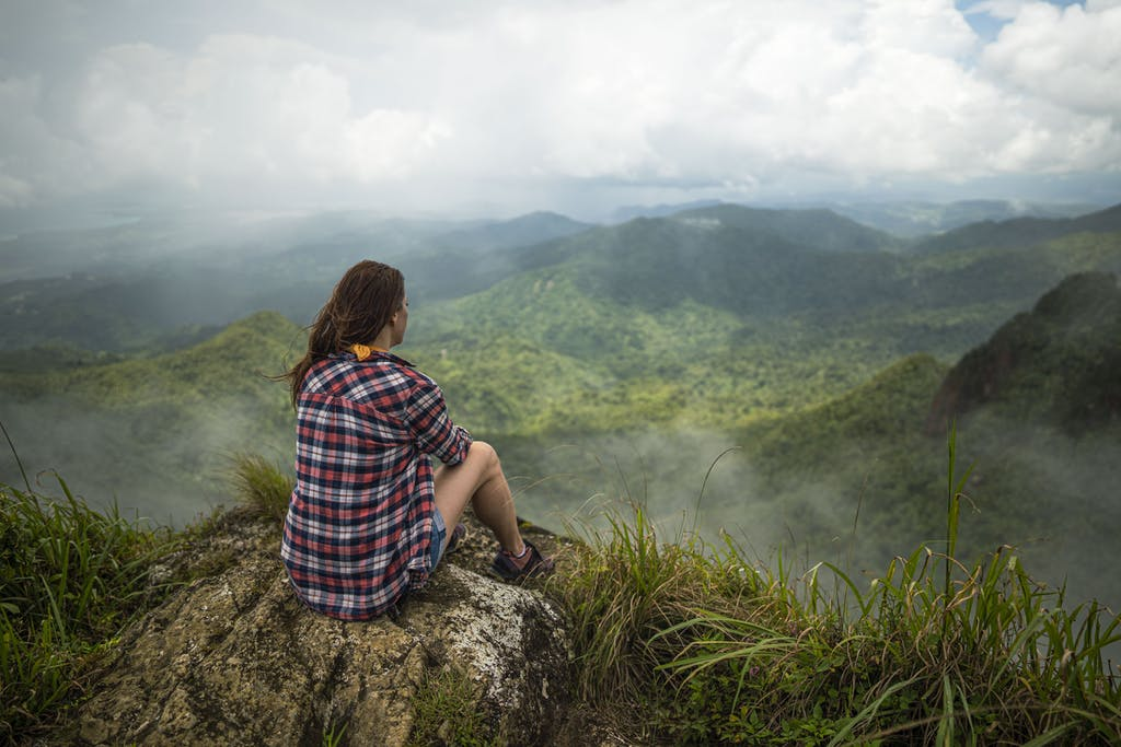 a woman sitting on a mountain looking at the landscape
