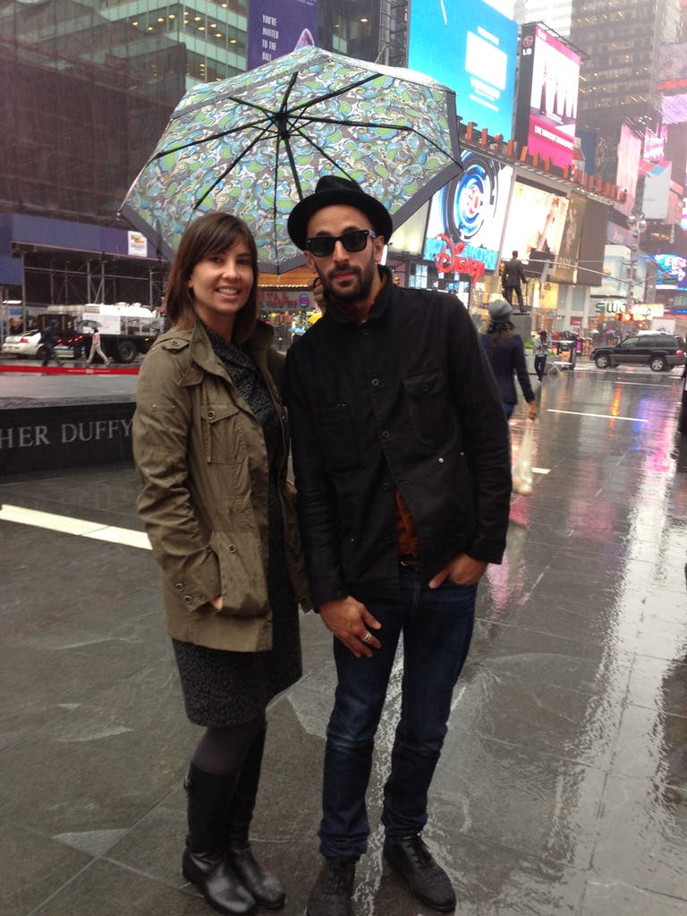 Lauren Beebe & JR in times square in the rain standing in the rain holding an umbrella