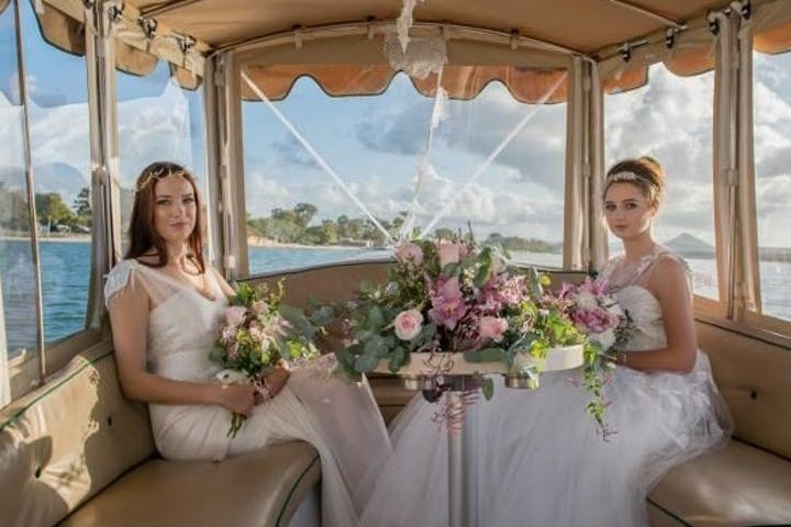 Bride and bridesmaid sitting riding electric boat in noosa