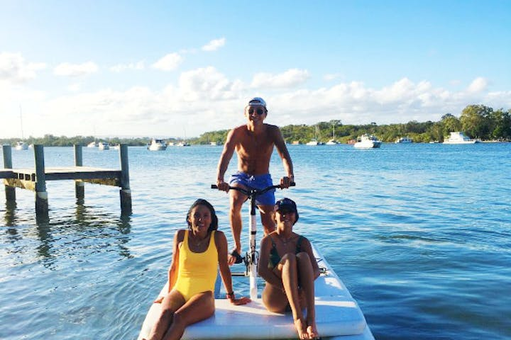 Family riding nauticycle water bike in noosa