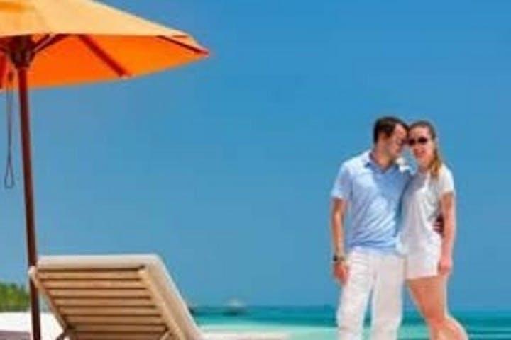 couple on beach next to umbrella