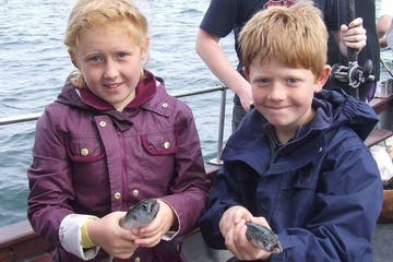 two children holding their fish