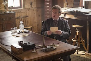 Colm Meaney sitting at a table
