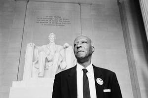 a man wearing a suit and tie with Lincoln Memorial in the background