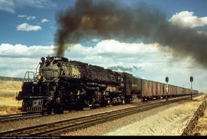 a large long train on a track with smoke coming out of it