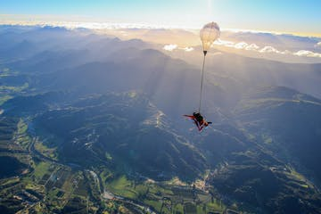 A person parachuting over the gorgeous mountains of Abel Tasman