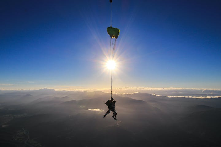 A person skydiving as the sun sets in the background