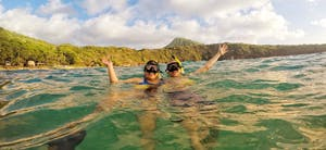 couple snorkeling at Hanauma Bay with Koko head in the background