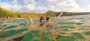 couple snorkeling at Hanauma Bay with Koko head in the background