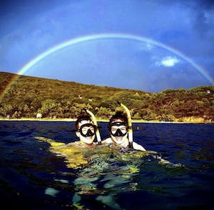 a couple smiling under a rainbow over Hanauma Bay