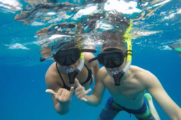 couple snorkeling in clear blue water at Hanauma Bay with Pure Aloha Adventures