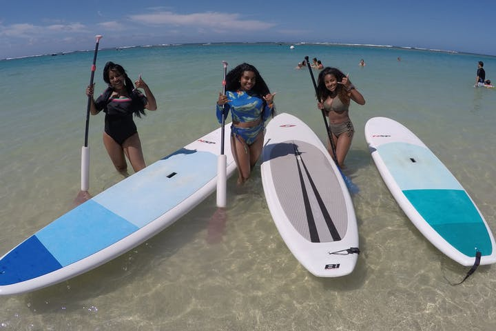 Three women standing next to paddleboards at Pure Aloha Adventures in Hawaii