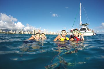Family of 4 snorkeling at Pure Aloha Adventures in Honolulu Hawaii with snorkel boat in the background