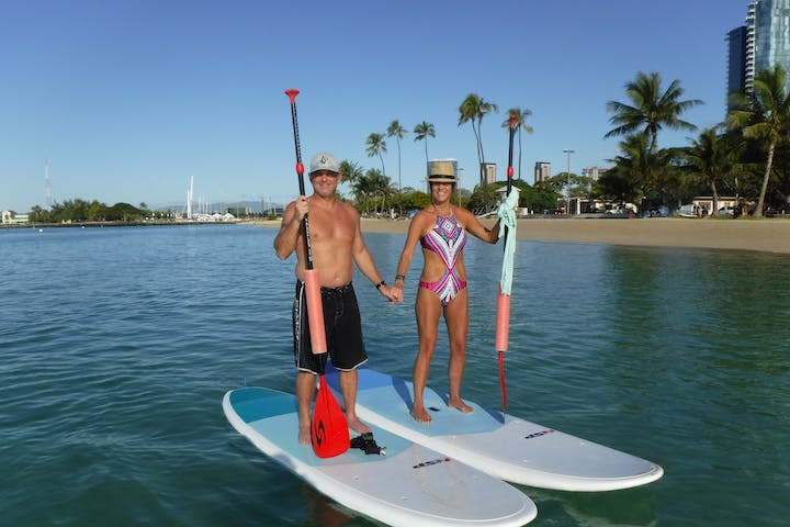 A fit couple holding hands on stand up paddle boards in Waikiki with Pure Aloha Adventures