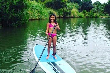 Young girl in a pink bikini posing while paddling SUP at Pure Aloha Adventures in Hawaii