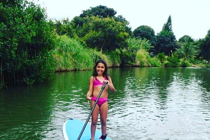 Young girl paddling SUP at Aloha Adventures in Hawaii