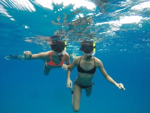 Two girls snorkeling in clear water at Pure Aloha Adventures in Oahu