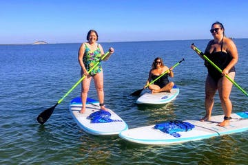 3 woman on stand up paddle boards with Dauphin Island bridge in the background