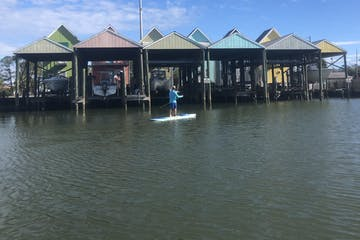 a man on a paddle board in front of colorful houses