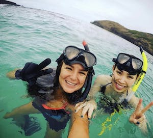2 girls with snorkeling masks on their heads standing in water and holding up peace signs