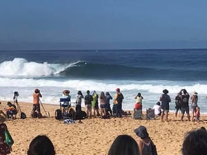 crowd of people standing on the beach watching large waves