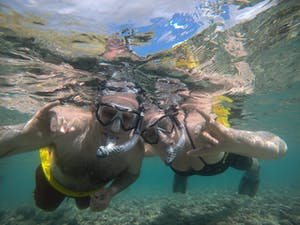 2 people snorkeling underwater with masks and snorkels
