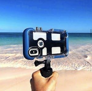 an iPhone in a waterproof case on a beach in Hawaii