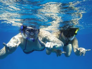 2 girls snorkeling in blue water