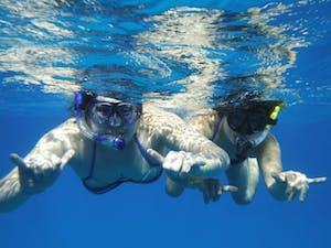 2 girls snorkeling in blue water