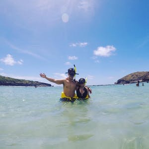 2 people in masks and snorkels standing in the water at Hanauma Bay in Hawaii