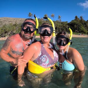 a group of people standing the water with snorkel gear on