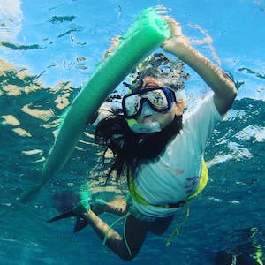 a girl snorkeling in Hawaii while holding a pool noodle