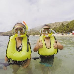 2 little kids standing in water while wearing life jackets and snorkel masks