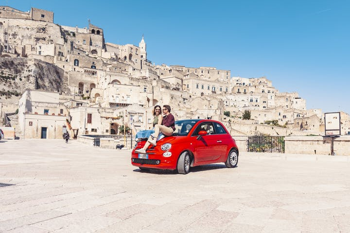 Couple sitting on red fiat 500