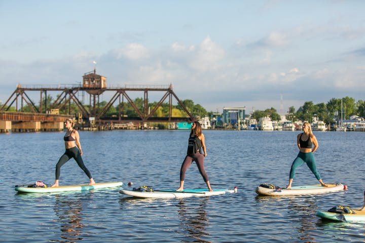 3 ladies doing stand up paddle board fitness class