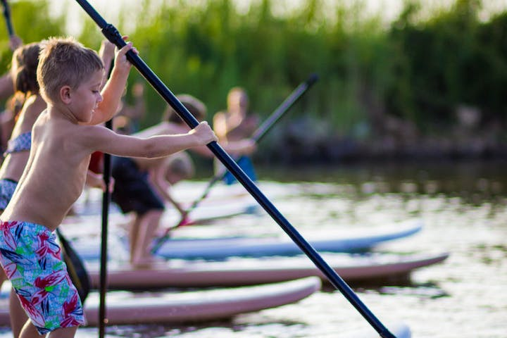 Kids doing stand up paddle boarding lessons