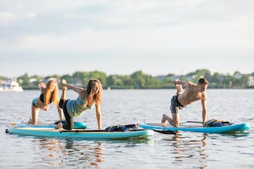 3 people doing paddle board training