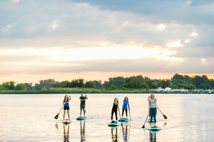 Group of people doing stand up paddle board tour