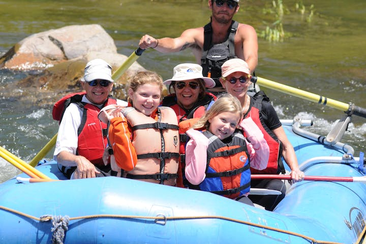 group of children and family smiling in raft